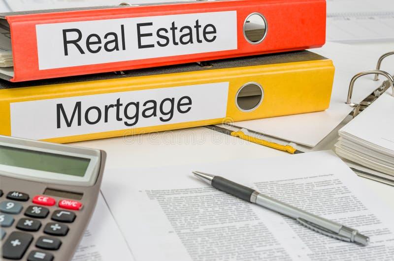 Mappar med etiketterna Real Estate och Mortgage royaltyfri bild