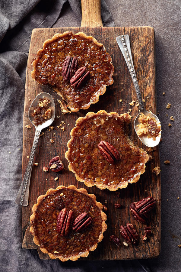 Mapple pecan tarts. Homemade mapple syrup and pecan tarts on wooden cutting board from top view stock photos