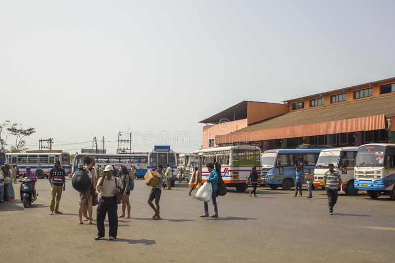 Indian people and tourists walk at the bus station amid parked colorful buses and buildings stock image