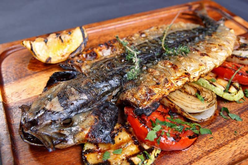 Maquereau cuit au four avec des légumes sur un conseil en bois image libre de droits