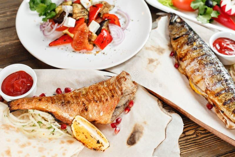 Maquereau et bar de mer grillés Salade des légumes frais Servir sur un conseil en bois sur une table rustique Barbecue photo libre de droits