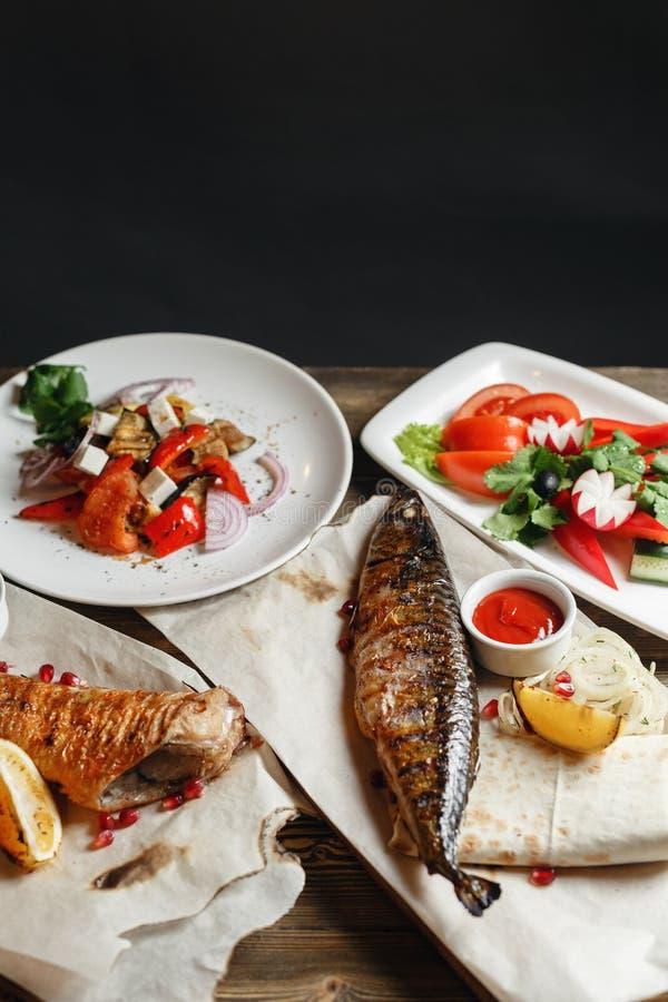 Maquereau et bar de mer grillés Salade des légumes frais Servir sur un conseil en bois sur une table rustique Barbecue photographie stock libre de droits