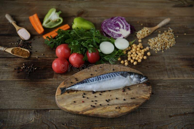 Maquereau frais d'isolement sur une planche à découper en bois avec des légumes, des haricots et des herbes poussées et des épice image libre de droits