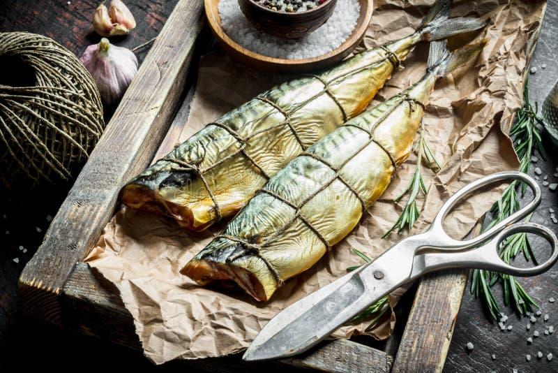Maquereau fumé de poissons sur un plateau avec la ficelle, les ciseaux et les épices images libres de droits