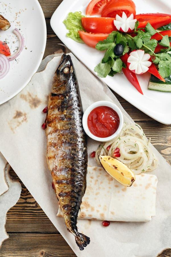 Maquereau grillé et une salade des légumes frais Servir sur un conseil en bois sur une table rustique Menu de rôtisserie image stock