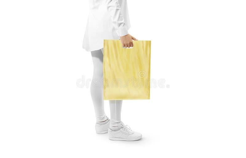 Maqueta amarilla en blanco de la bolsa de plástico que lleva a cabo la mano fotografía de archivo libre de regalías