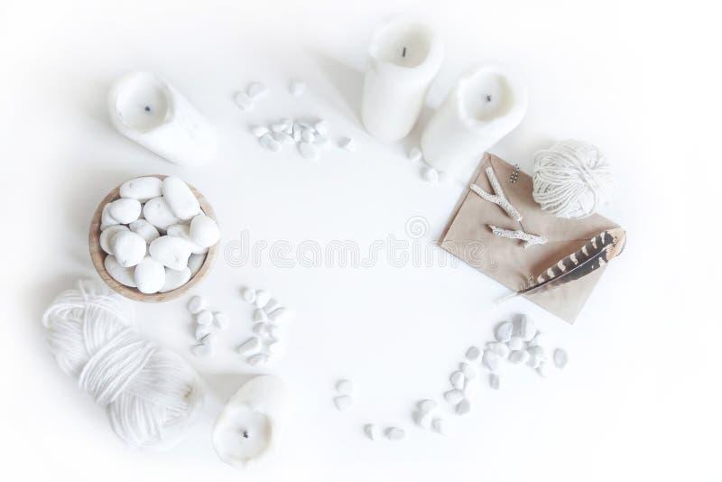 Maqueta blanca de Boho con las velas, el hilo de algodón, las plumas y el guijarro del mar blanco en el escritorio Endecha del pl imágenes de archivo libres de regalías