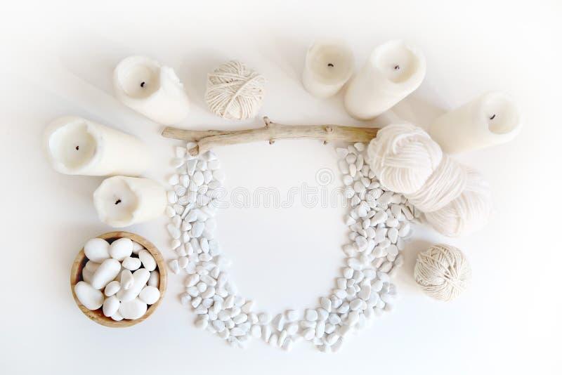 Maqueta blanca de Boho con las velas, el hilo de algodón y el guijarro del mar blanco en el escritorio Endecha del plano de la vi fotografía de archivo libre de regalías