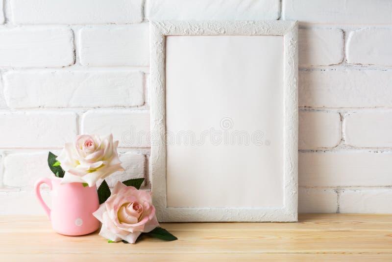 Maqueta blanca del marco con dos pálidos - rosas rosadas fotos de archivo