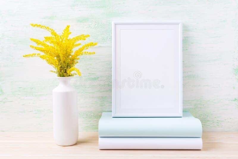 Maqueta blanca del marco con la hierba y los libros de oro ornamentales imagen de archivo libre de regalías