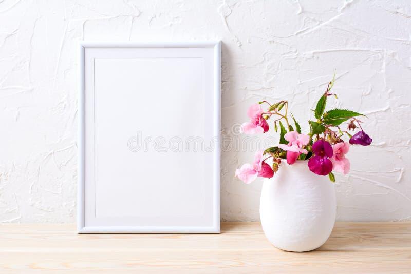 Maqueta blanca del marco con las plantas rosadas de la casa en maceta foto de archivo libre de regalías