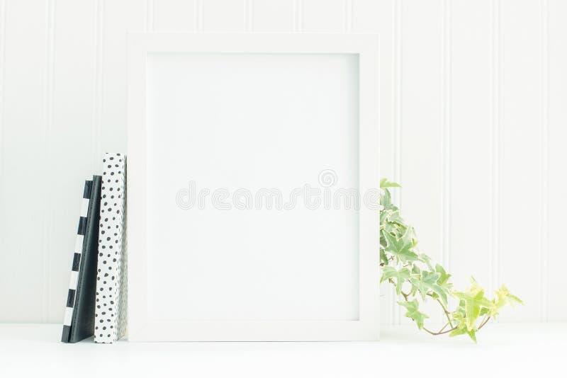 maqueta blanca del marco 8x10 con los cuadernos y la hiedra blancos y negros imagen de archivo
