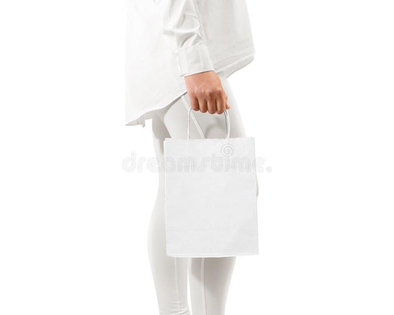 Maqueta blanca en blanco de la bolsa de papel del arte que lleva a cabo la mano, trayectoria de recortes imágenes de archivo libres de regalías