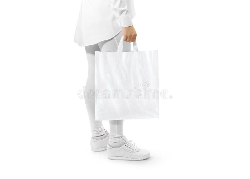 Maqueta blanca en blanco de la bolsa de plástico que lleva a cabo la mano foto de archivo libre de regalías