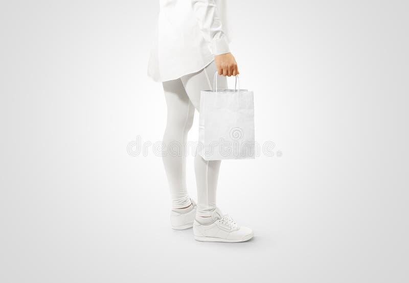 Maqueta blanca en blanco del diseño de la bolsa de papel del arte que lleva a cabo la mano imagenes de archivo
