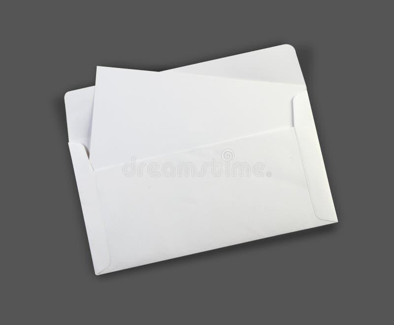 Maqueta blanca en blanco del sobre con una tarjeta de la invitación imagen de archivo