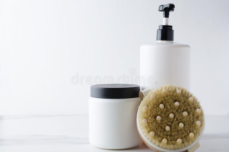Maqueta, botellas de los cosméticos, cepillo del cuerpo para la piel de limpieza Cuerpo, concepto del cuidado del cabello fotos de archivo