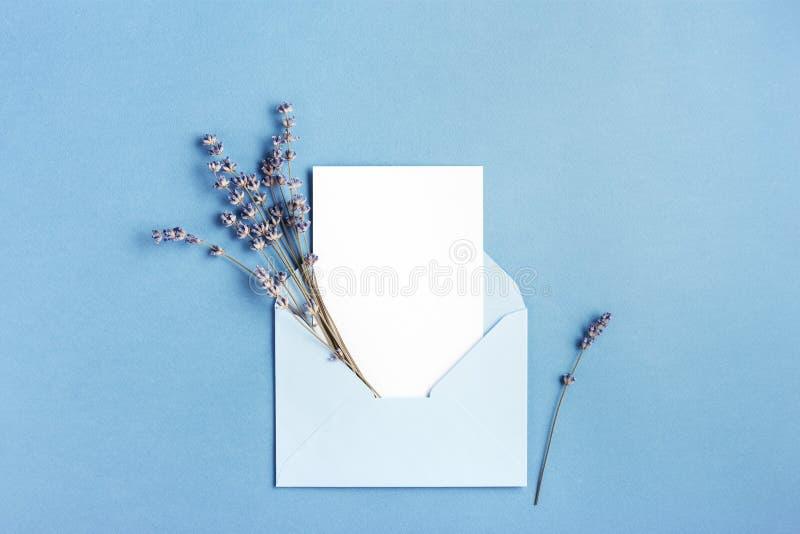 Maqueta con la tarjeta en sobre azul fotos de archivo