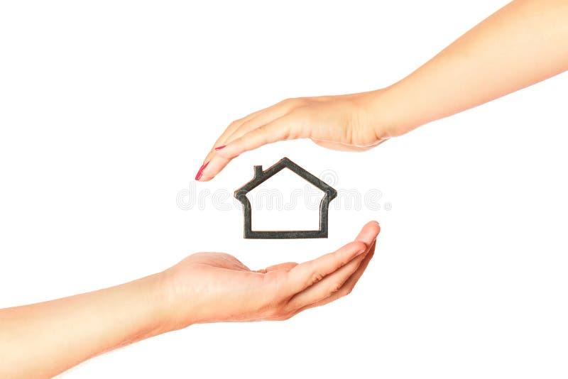 Maqueta de la casa entre el hombre y las manos de la mujer imagen de archivo libre de regalías
