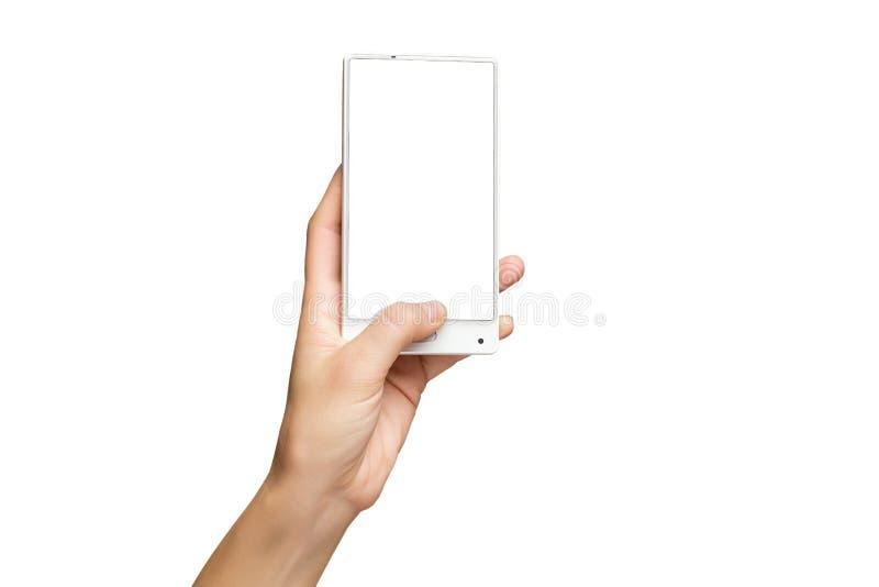 Maqueta de la mano femenina que sostiene el teléfono celular frameless con la pantalla en blanco foto de archivo