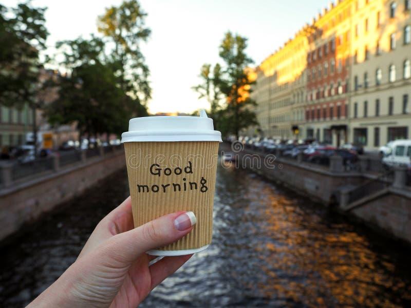 Maqueta de la mano femenina que sostiene una taza para llevar del papel del café en el fondo del río con el espacio de la copia foto de archivo