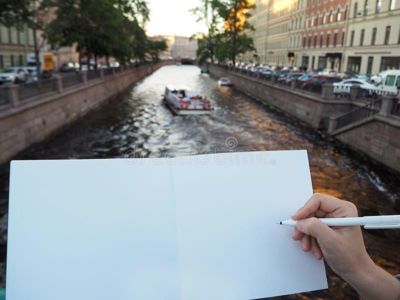 Maqueta de la mano de la persona que sostiene el cuaderno blanco en blanco que se prepara para anotar el suyo o el suyo ideas imagen de archivo libre de regalías