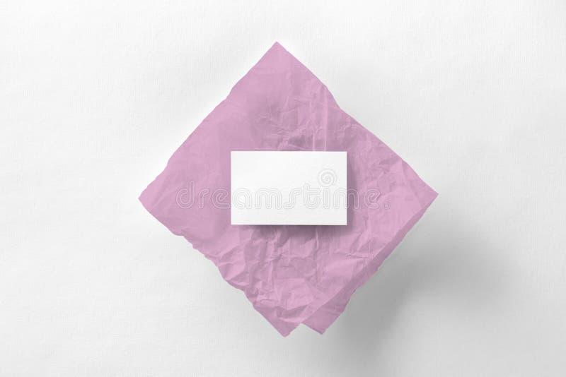 Maqueta de la tarjeta de visita en el papel de trazo rosado en el blanco texturizado foto de archivo