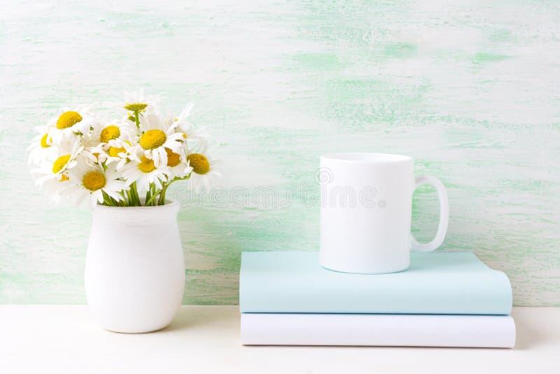 Maqueta de la taza del café con leche con el ramo blanco de la manzanilla de campo en la ha fotos de archivo libres de regalías