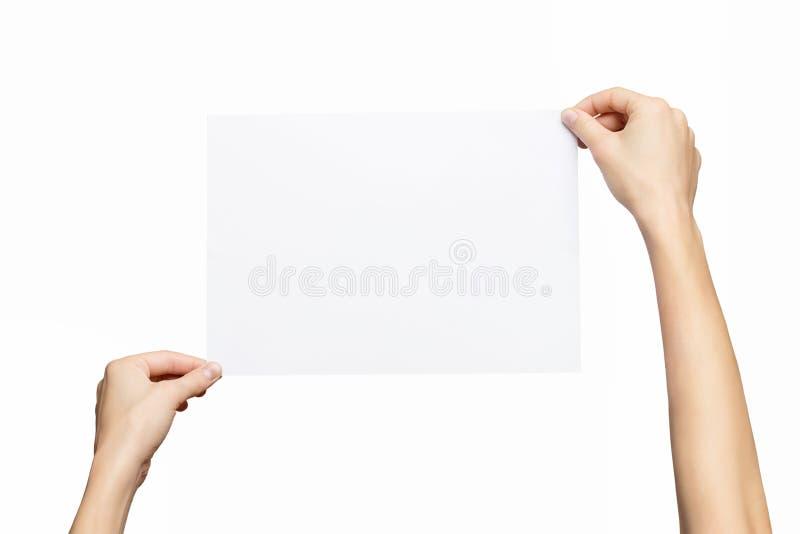 Maqueta de las manos femeninas que llevan a cabo la lista del papel en blanco aislada en el fondo blanco imagenes de archivo