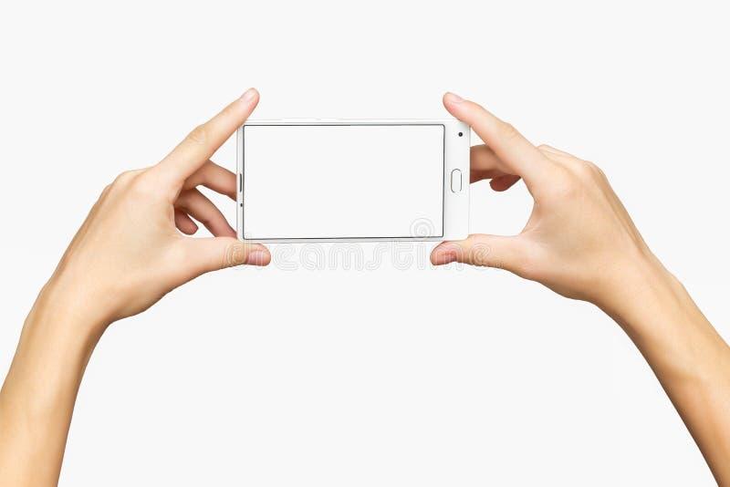 Maqueta de las manos femeninas que sostienen el teléfono móvil con la pantalla blanca fotos de archivo libres de regalías