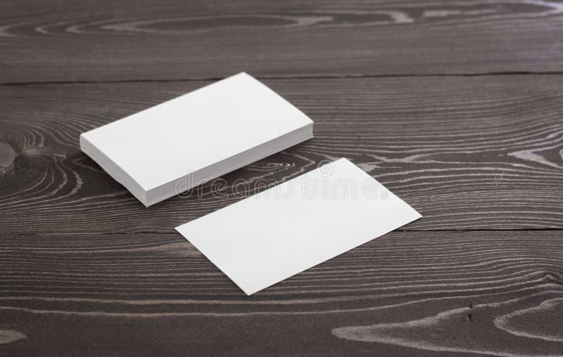 Maqueta de las tarjetas de visita en un fondo de madera oscuro Plantilla para la identidad de marcado en caliente foto de archivo