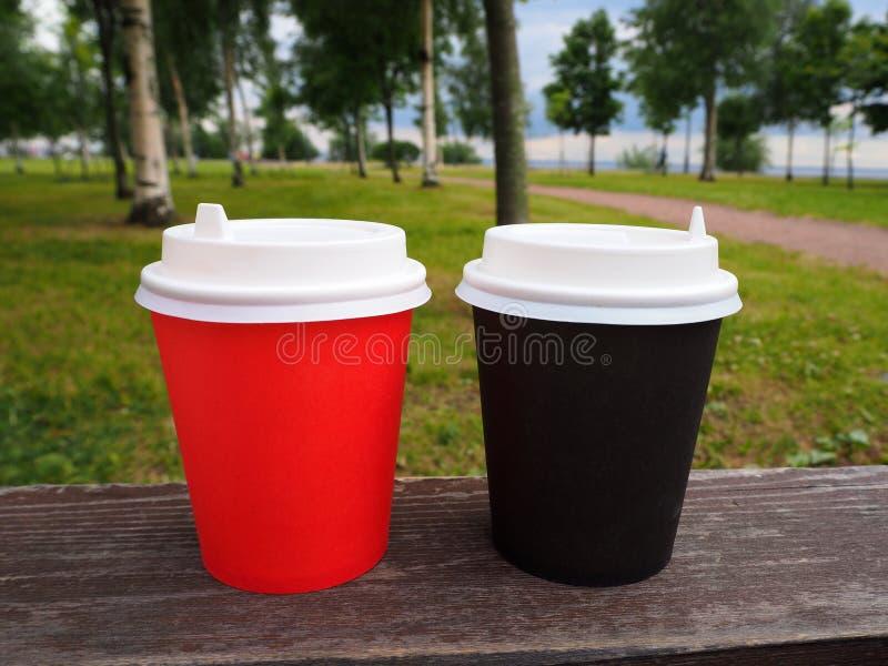 Maqueta de las tazas de café para llevar del papel rojo y marrón en superficie de madera en fondo natural del parque del verano imagenes de archivo