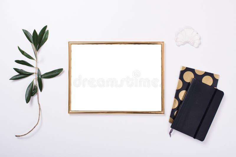 Maqueta de oro del marco en el tablero de la mesa blanco imágenes de archivo libres de regalías