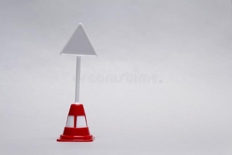Maqueta de una señal de tráfico triangular miniatura en un fondo ligero imagen de archivo libre de regalías