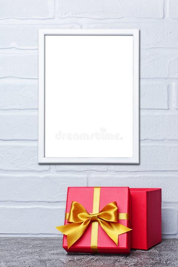 Maqueta del bastidor blanco con el espacio de la copia para el cartel y la caja de regalo clásica roja con el lazo de satén de or fotografía de archivo libre de regalías