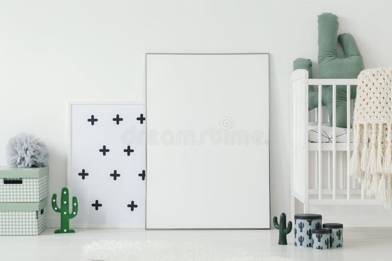 Maqueta del cartel vacío blanco al lado de la cuna en interi del sitio del ` s del niño foto de archivo