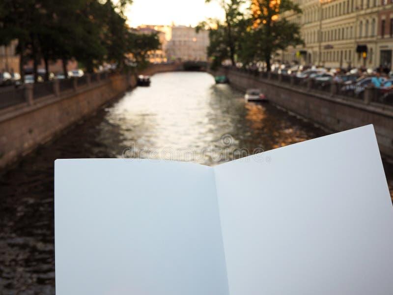 Maqueta del cuaderno en blanco con el espacio de la copia en el fondo del río de la ciudad foto de archivo