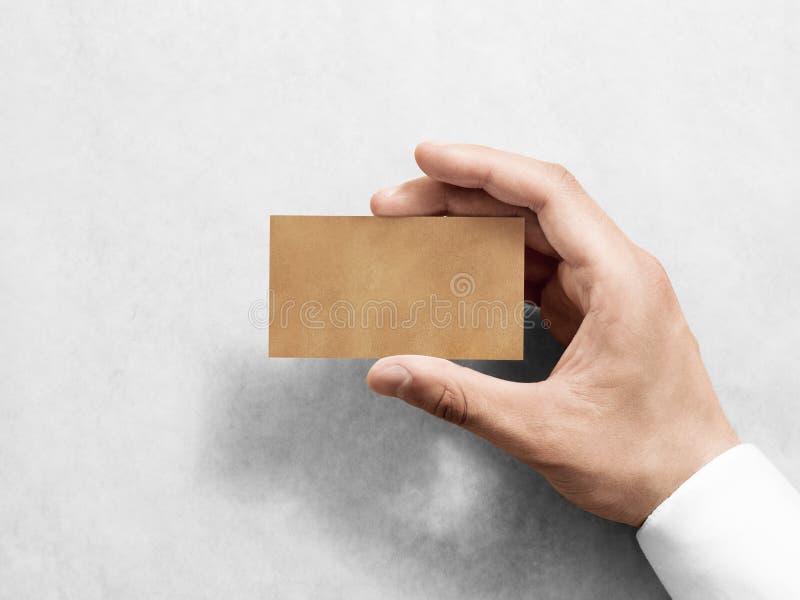 Maqueta del diseño de la tarjeta de visita de Kraft del llano del espacio en blanco del control de la mano imagen de archivo libre de regalías