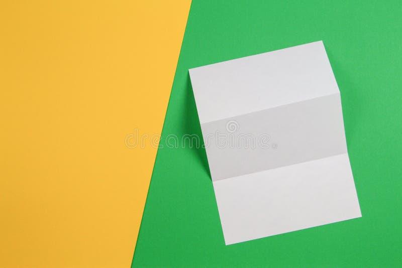Maqueta del folleto triple blanco del folleto del espacio en blanco sobre fondo verde y amarillo fotografía de archivo