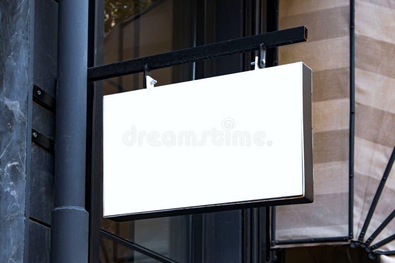 Maqueta del letrero y marco vacío de la plantilla para el logotipo o texto en el fondo exterior de la tienda de la ciudad de la p foto de archivo