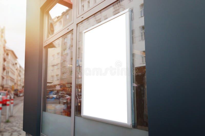 Maqueta del marco del cartel en la ventana de la tienda en calle de la ciudad fotos de archivo