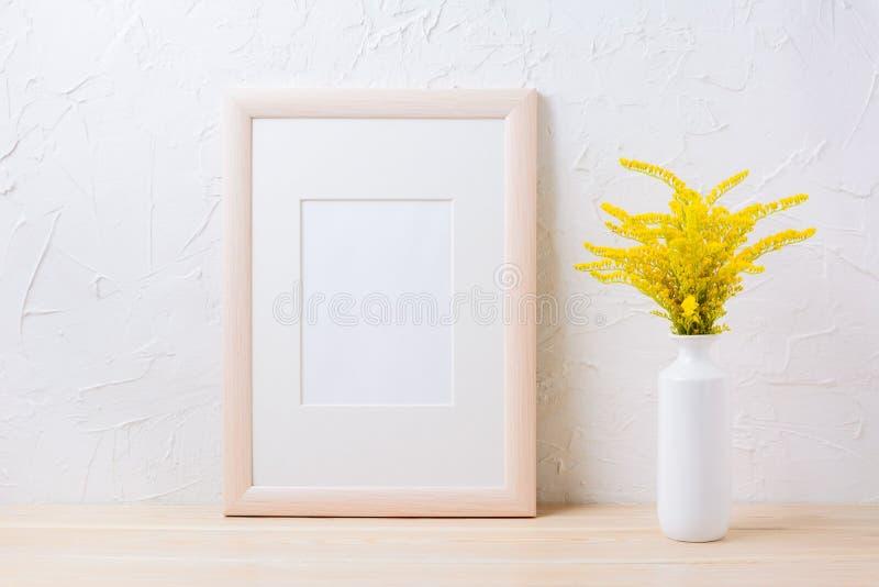Maqueta del marco de madera con la hierba floreciente amarilla ornamental en el va imagenes de archivo