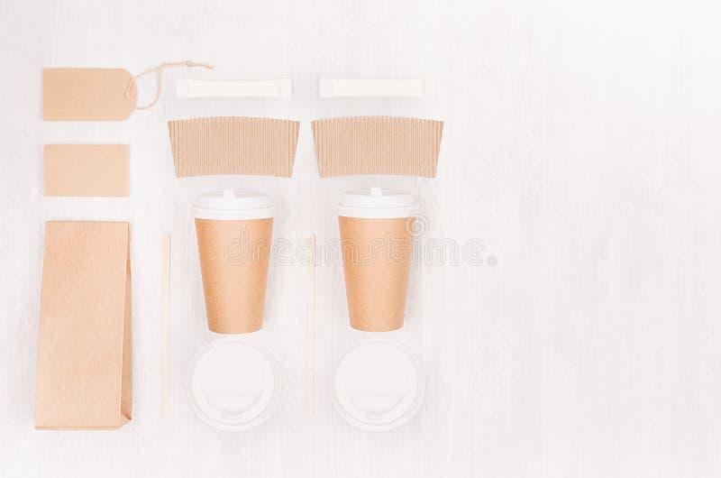 Maqueta determinada para llevar para la marca - dos tazas de papel marrones del café con la tarjeta en blanco, etiqueta, paquete, imagen de archivo