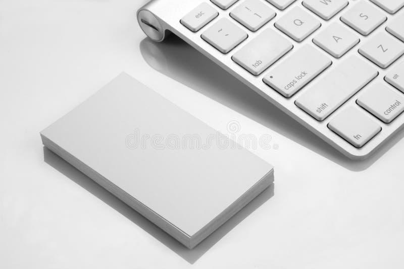 Maqueta en blanco de la tarjeta de visita con un teclado en el fondo blanco fotos de archivo libres de regalías