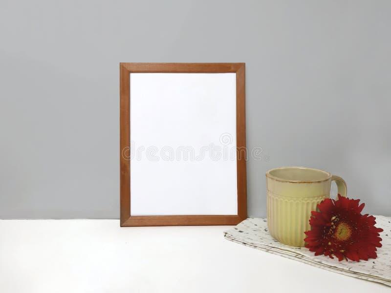 Maqueta en blanco del marco en la tabla sobre la pared de piedra imagenes de archivo