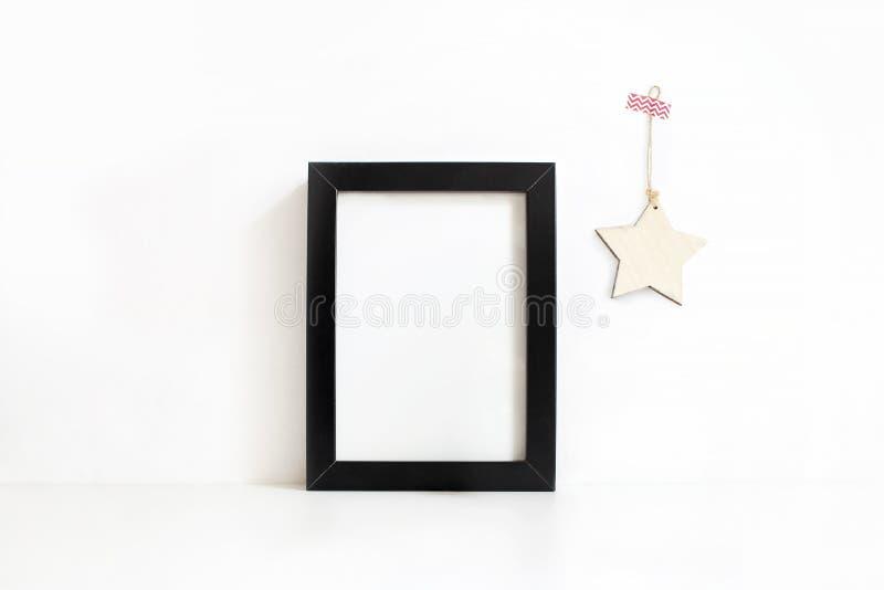 Maqueta en blanco negra vertical del marco de madera en la tabla blanca Decoración de madera de la estrella que cuelga en la pare foto de archivo