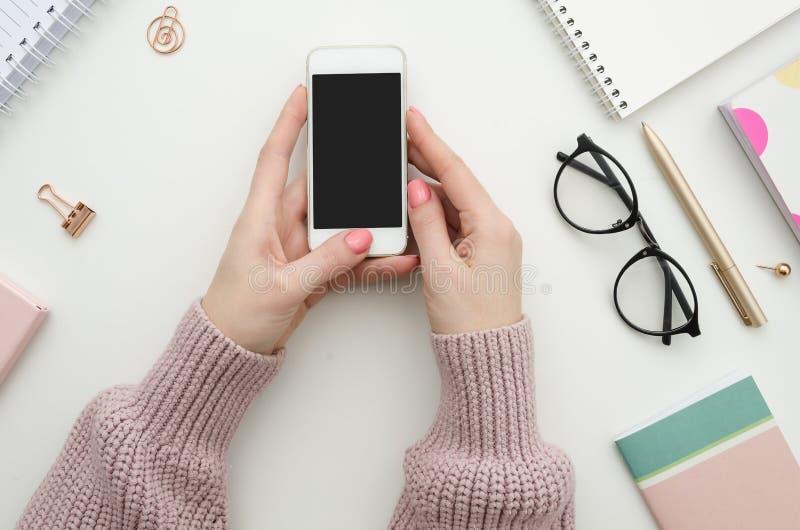 Maqueta femenina del espacio de trabajo con smartphone en manos, cuaderno, gafas, libreta, pluma y materiales de oficina femenino foto de archivo
