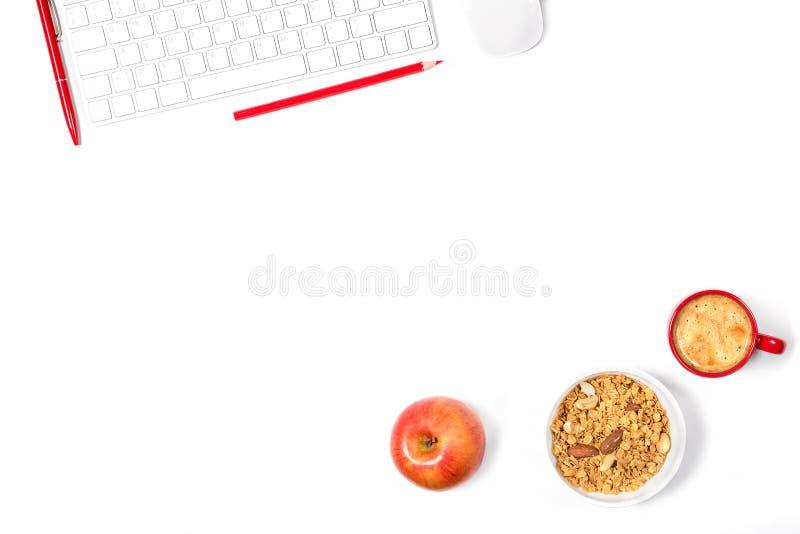 Maqueta mínima hermosa Teclado moderno blanco, ratón, lápiz, pluma, placa con el granola, pequeña taza de café roja en el backgro fotos de archivo libres de regalías