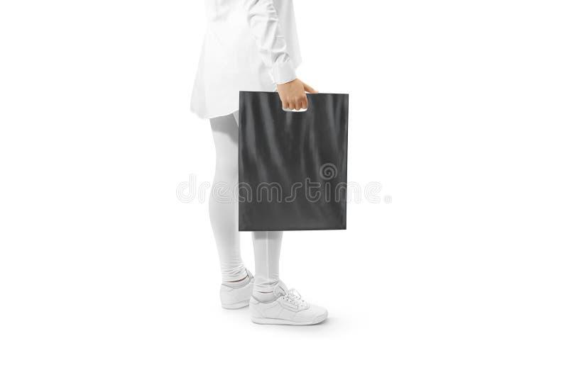 Maqueta negra en blanco de la bolsa de plástico que lleva a cabo la mano imagenes de archivo