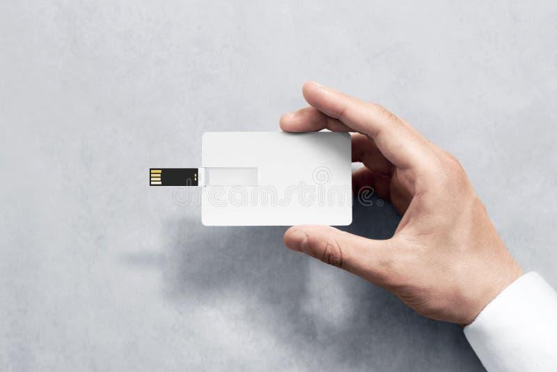 Maqueta plástica blanca en blanco del diseño de tarjeta del usb de la oblea que lleva a cabo la mano imagen de archivo libre de regalías